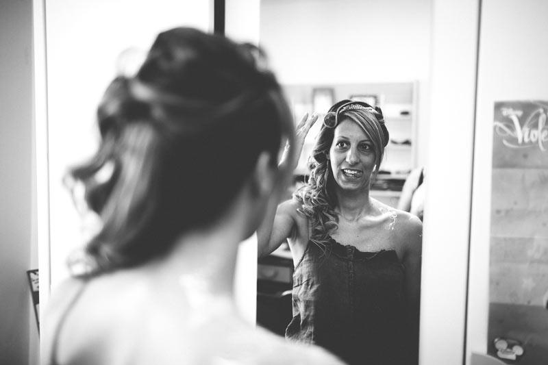 la mariée se regarde dans le miroir sous l'oeil du photographe