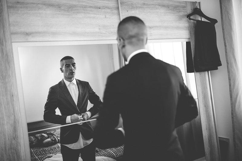 le marié enfile son costume dans sa chambre