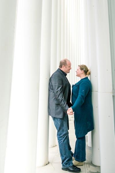 couple holding hands between columns