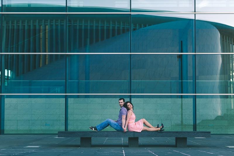 couple sitting on bench in front of the opera of luxembourg