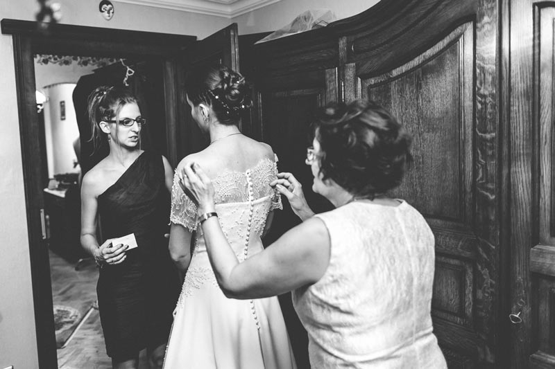 family members adjusting the wedding dress of the bride