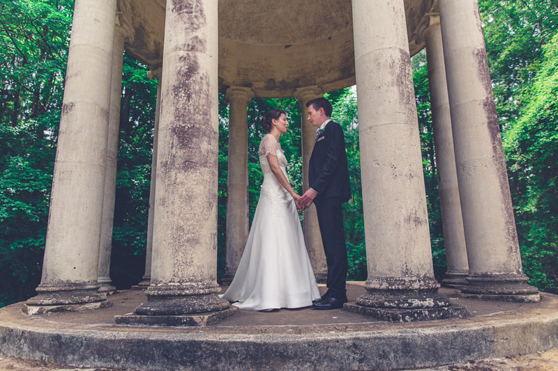groom and bride holding hands below a dome