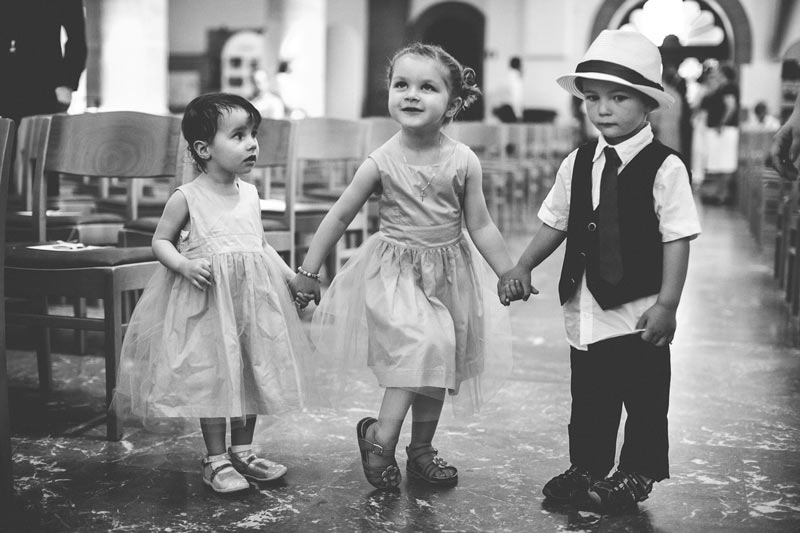 children holding hands during the wedding ceremony in church