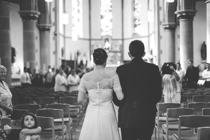 bride holding her father's arm while walking down the alley of church