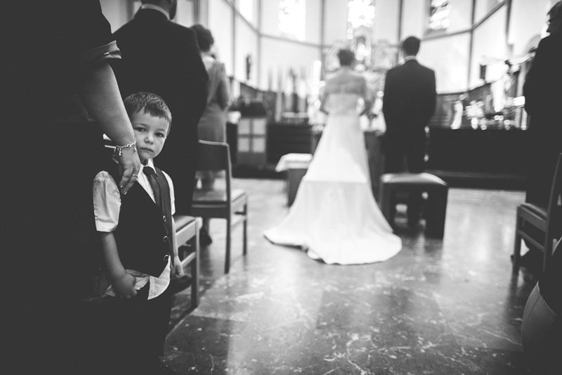 kid staring at the photographer during wedding ceremony