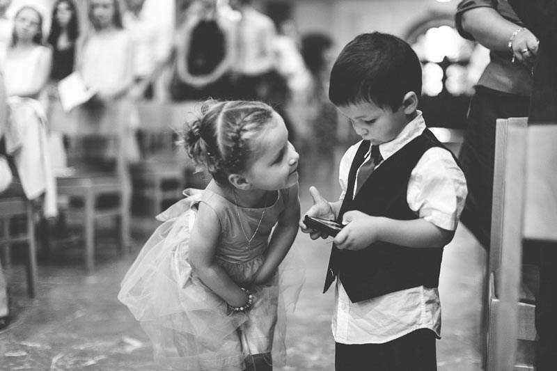 little girl looking at boy playing with his video game during wedding ceremony