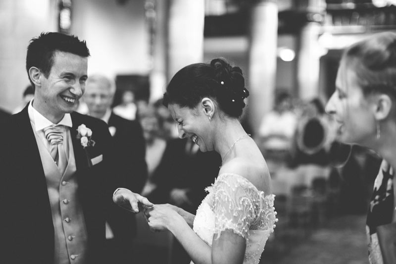 bride and groom laughing when wedding ring is too small to fit finger