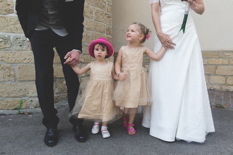 kids holding hands with bride and groom
