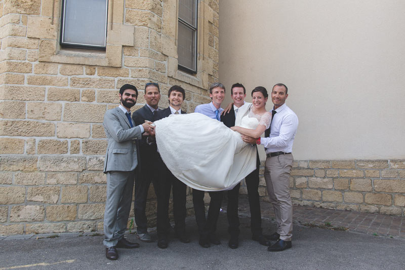 guests carry the bride for group photo