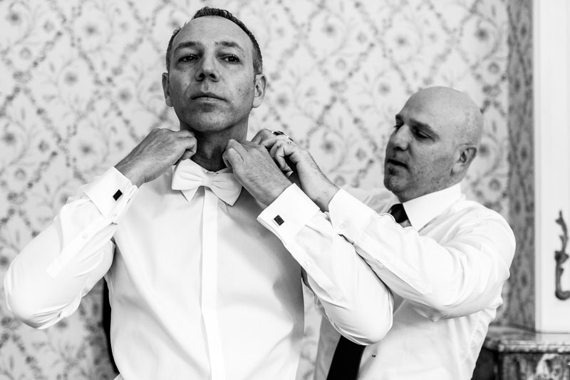 adjusting the shirt of the groom