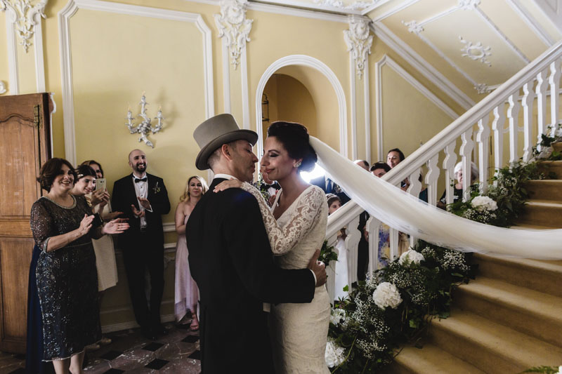 newlyweds kissing in castle staircase