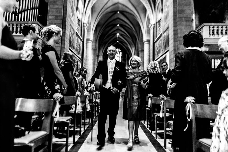 the groom walking down the church with his mom