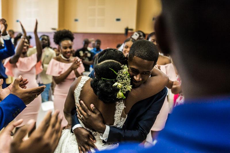 les mariés se serrent dans les bras sous le regard de leurs proches