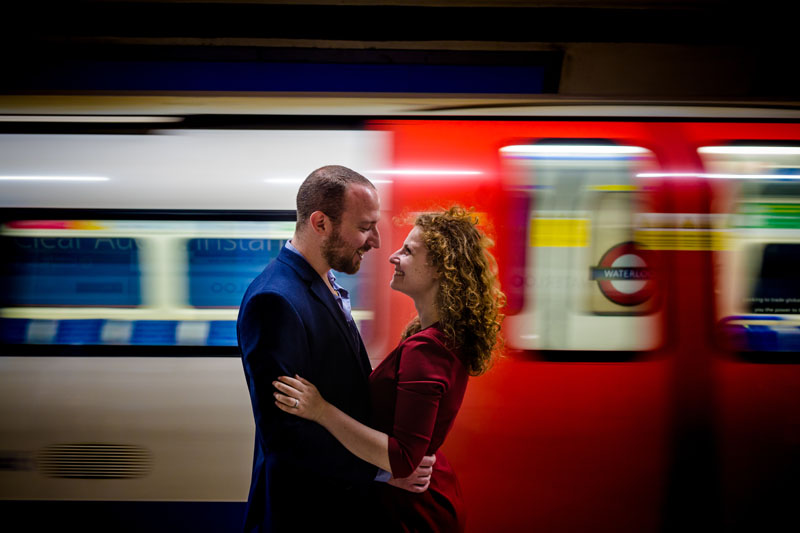 engaged couple posing in front of the train at waterloo tube station in london