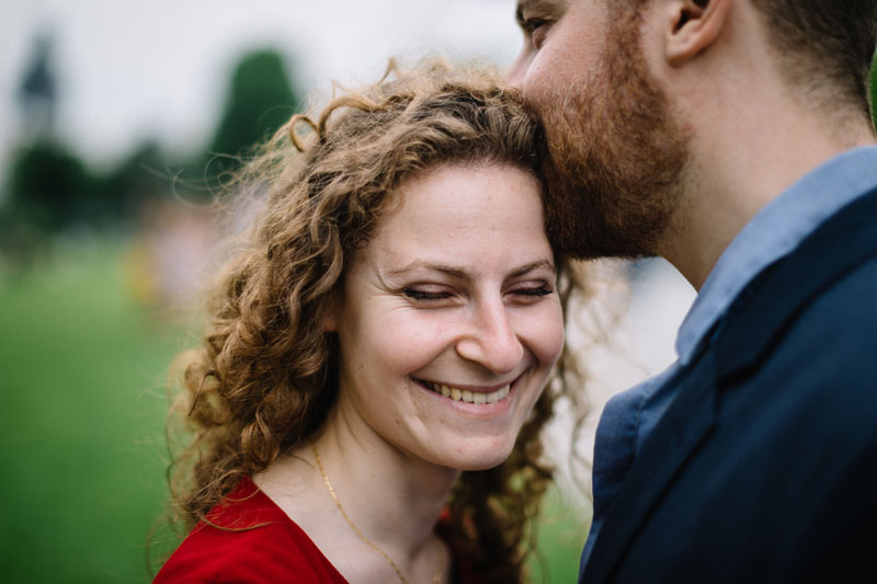 girl smiling as her fiancé kisses her