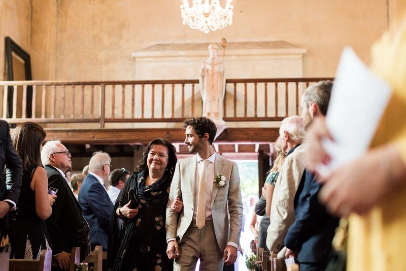 le marié entre dans l'église au bras de sa maman