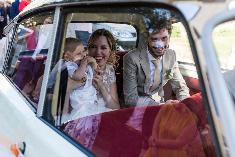 les mariés et leur bébé dans la voiture