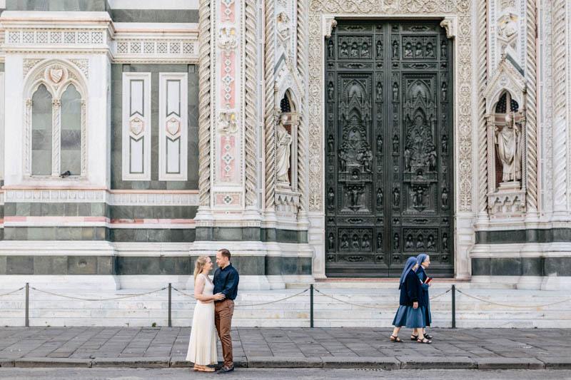 deux nones marchent pendant qu'un couple s'enlasse à florence